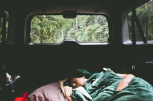 man in a sleeping bag sleeping in the back of his car