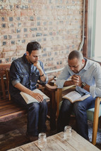 men praying and reading Bibles at a Bible study