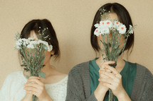 girls holding bouquets of daisies