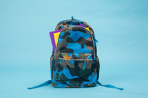Boy's camo backpack on light blue background.