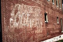 vintage coca-cola sign on a brick wall