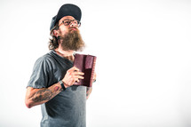 man with tattoos holding a Bible and looking up to God