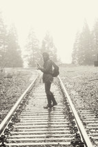 a woman backpacking standing on railroad tracks in the fog on a winter morning