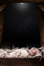 baby Jesus under the stars in a manger