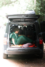 man in a sleeping bag in the back of his car