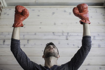 man wearing boxing gloves with raised hands