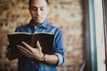 Latino man reading a Bible standing