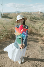 woman holding up a flower wind spinner