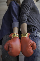 couple wearing boxing gloves standing back to back