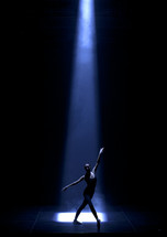 dancer under a spot light on stage