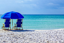 Two blue chairs under an umbrella overlooking Gulf of Mexico