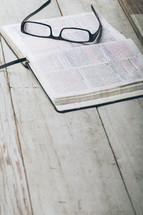 Reading glasses on pages of open Bible laying on wooden table.