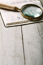 magnifying glass on the pages of a Bible - searching for clarity