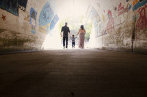 a young family walking through a tunnel