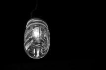 Light in a jar shining in the darkness. Monochrome.