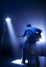 Light shines on a guitarist on stage