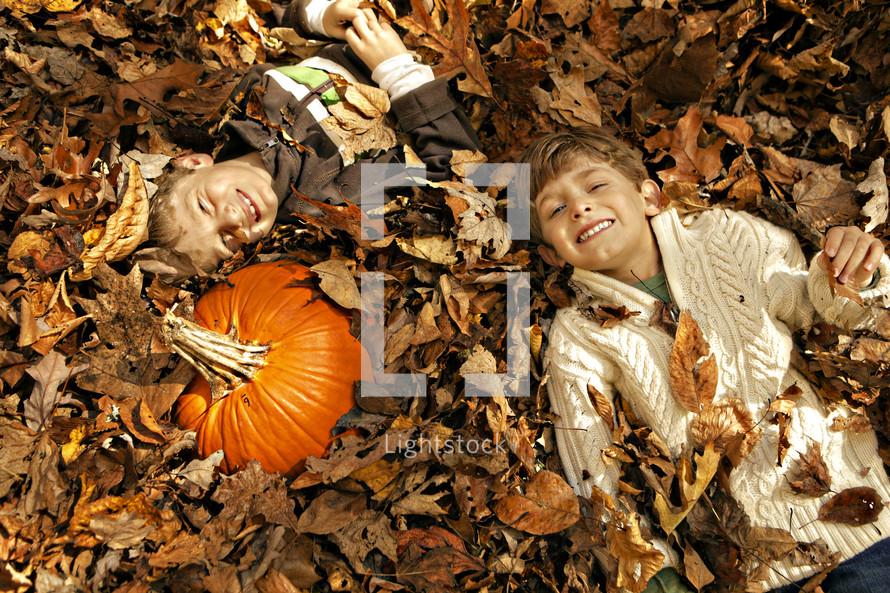 boys lying in a leaf pile