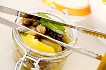 Jar of olives peaches bay leaves tongs
