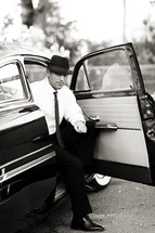 man in a suit and hat getting out of an old car vintage 1950's men