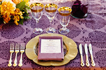 Formal dinner setting at table purple gold orange
