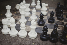 White and black chess pieces sit atop a highly used chess board.