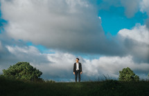 a man standing under the clouds on top of a hill