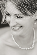 Smiling woman in net veil with pearl necklace and earrings bride wedding