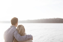 couple standing together by a lake