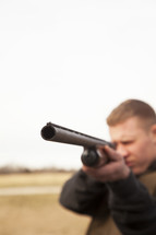 a man pointing a shotgun
