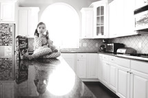 a girl child in pajamas sitting on a kitchen counter
