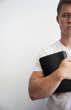 man holding a Bible to his chest