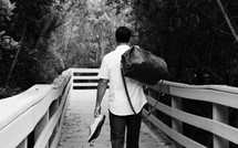 a man with a bag and shoes walking down a wooden path