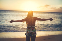 woman standing on a beach at sunset with open arms