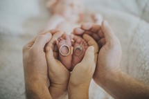 a mother and father holding the feet of their newborn baby