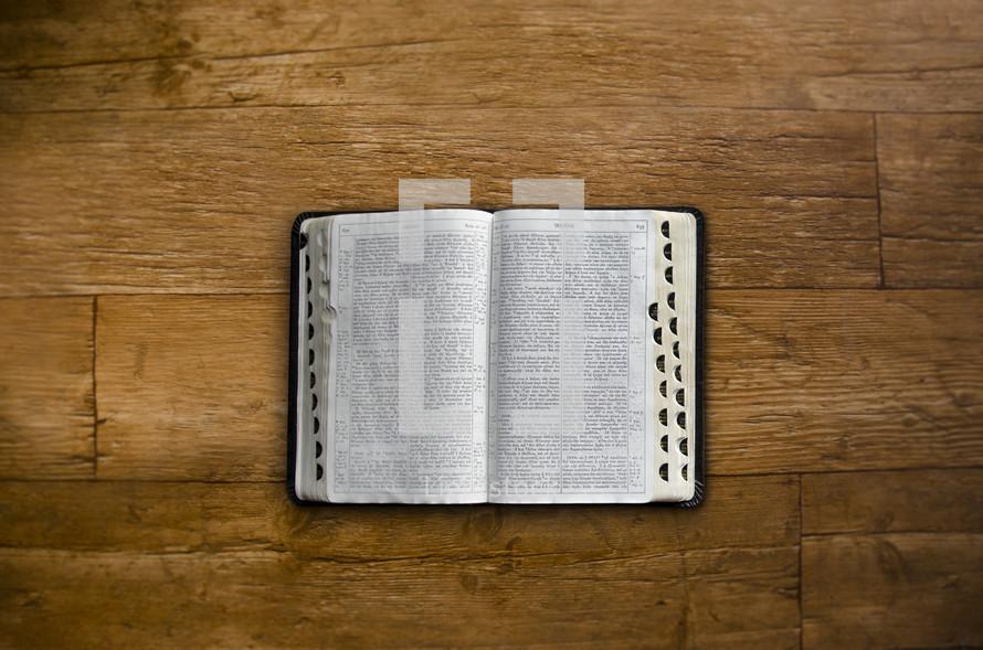 open bible on a wood floor