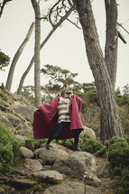 Woman in a red cape looking through binoculars, standing on a rock in a tree-filled forest.