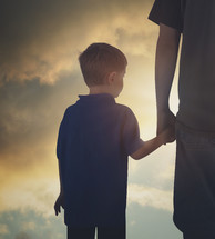 father holding his son's hand