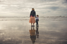 a mother and son walking on a beach