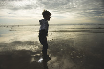 toddler boy playing in puddles on a beach