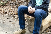 legs of a boy sitting on a log
