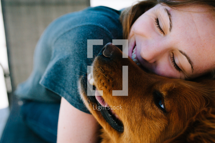 a girl hugging her dog