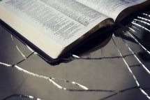 Bible on top of cracked glass.