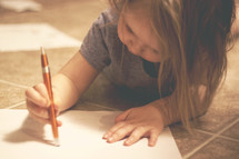 a toddler writing with a pen