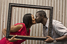 Couple kissing behind empty picture frame