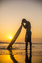 surfer with his head bowed in prayer over his surfboard