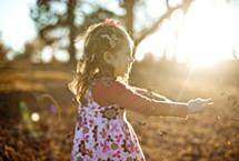 girl tossing fall leaves