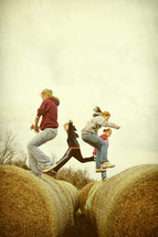 Children jumping across barrels of hay.