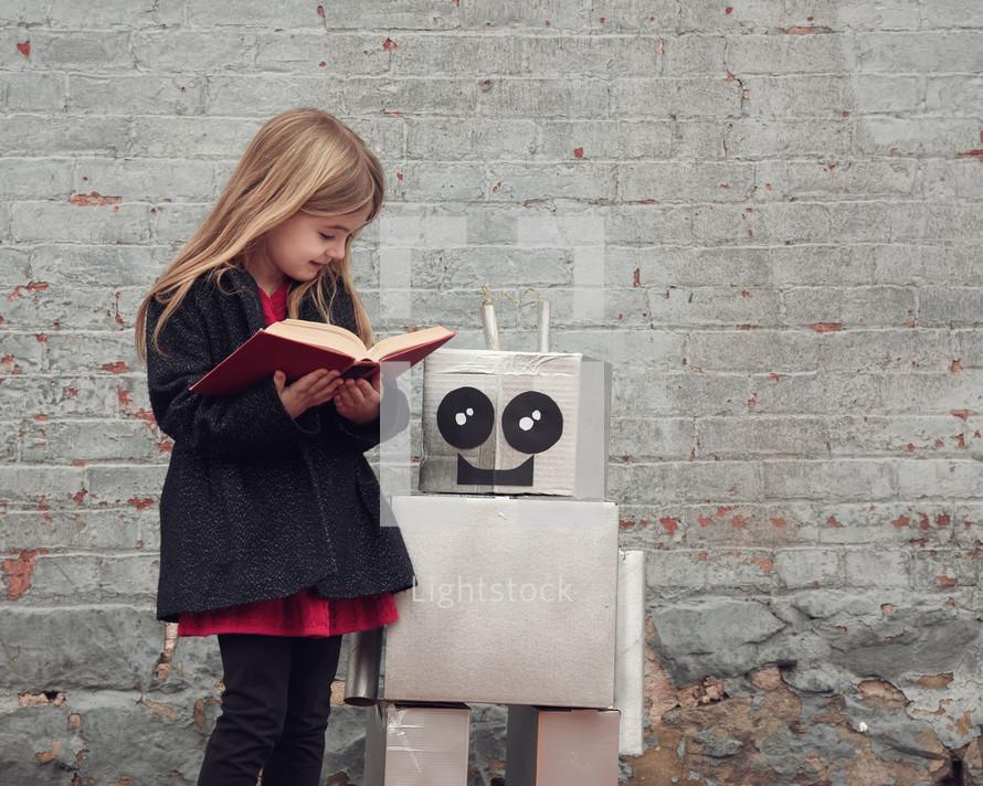 a girl reading a book to a robot