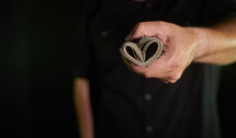 Person holding money shaped like a heart