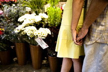Couple holding hands in flower shop